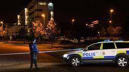 Petugas berjaga di areal kantor polisi yang meledak di Helsingborg, Swedia (18/10). Menurut kepolisian setempat, ledakan tersebut belum diketahui penyebabnya. (AFP Photo/TT News Agency /Johan Nilsson/Sweden Out)