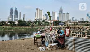 Pedagang berjualan makanan ringan di bantaran Kanal Banjir Barat dengan latar belakang gedung pencakar langit di Jakarta, Kamis (6/8/2020). BPS mencatat pertumbuhan ekonomi Indonesia Kuartal II/2020 minus 5,32 persen akibat perlambatan sejak adanya pandemi COVID-19. (merdeka.com/Iqbal S. Nugroho)