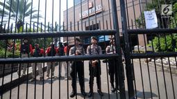 Petugas polisi berjaga di depan Gedung Maspion Plaza, Jakarta Utara, Selasa (4/7). Mereka mununtut pihak Grab untuk mencairkan bonus Lebaran 2017 yang dijanjikan pihak perusahaan jika tetap bekerja selama libur Lebaran. (Liputan6.com/Gempur M Surya)