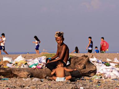 Anak-anak menyortir sampah di permukiman kumuh di sepanjang garis Pantai Baseco di Manila, Filipina (28/9/2019). Daerah memiliki pantai yang sering dikunjungi beberapa warga Manila meskipun tingkat coliform berbahaya di perairan yang berdekatan. (AFP Photo/Maria Tan)