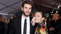 Kemesraan Miley Cyrus dan Liam Hemsworth di karpet merah premier film 'Thor: Ragnarok' di California, 10 Oktober 2017. Miley terlihat begitu manja saat meletakkan kepalanya di pundak pemain film THE HUNGER GAMES itu. (Rich Polk/Getty Images/AFP)