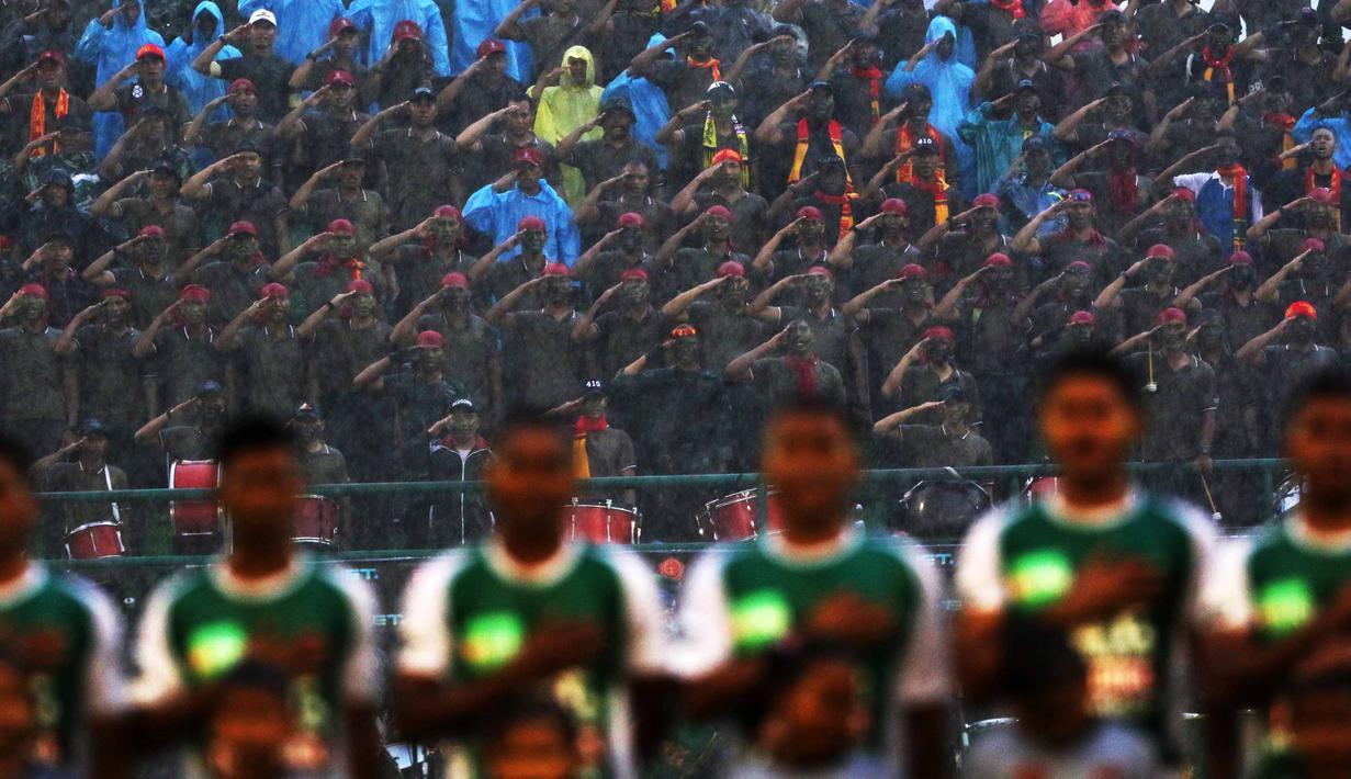 Suporter PS TNI melakukan penghormatan saat menyanyikan lagu Indonesia Raya bersama pemain PS TNI pada laga Piala Jenderal Sudirman di Stadion Manahan, Solo, Sabtu (12/11/2015). (Bola.com/Nicklas Hanoatubun)