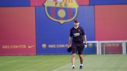 Pelatih Barcelona, Ernesto Valverde berjalan saat menghadiri latihan tim di Joan Gamper Sports City, Spanyol (16/9/2019). Barcelona akan menghadapi wakil Jerman, Borussia Dortmund pada grup F Liga Champions di Signal Iduna Park. (AFP Photo/Pau Barrena)