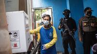 Polisi bersenjata bersiaga saat pekerja menurunkan vaksin COVID-19 produksi Sinovac dari truk setibanya di Surabaya pada Senin (4/1/2021).  Pemerintah mulai mendistribusikan 3 juta dosis vaksin Covid-19 asal perusahaan China, Sinovac, ke 34 provinsi Indonesia. (Photo by Juni Kriswanto / AFP)