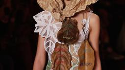 Seorang model mengenakan kertas cokelat atau yang biasa disebut kertas pembungkus di kepalanya saat membawakan rancangan karya Ronaldo Fraga dalam Sao Paulo Fashion Week di Brasil (26/4). (AP Photo / Andre Penner)
