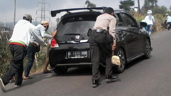 Personel Polsek Ibun membantu mendorong kendaraan roda empat yang tak kuat menanjak di kawasan Kamojang, Kabupaten Bandung. (Liputan6.com/Huyogo Simbolon)