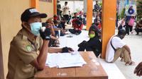 Warga mengantre untuk mendapatkan bantuan sosial (bansos) yang diberikan Pemerintah Provinsi Banten di Pinang, Tangerang, Jumat (1/5/2020). Bansos berupa uang tunai sebesar Rp 600 ribu tersebut diberikan kepada warga yang terdampak virus corona COVID-19. (Liputan6.com/Angga Yuniar)