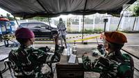 Tenaga kesehatan melapor kepada penjaga saat mengantarkan pasien positif Covid-19 di salah satu pintu masuk Runah Sakit Darurat (RSD) Wisma Atlet, Kemayoran, Jakarta, Minggu (30/5/2021). (merdeka.com/Iqbal S. Nugroho)