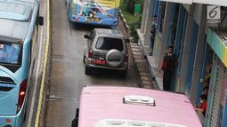Penumpang menunggu bus transjakarta di Jalan MH Thamrin, Jakarta, Kamis (31/5). Tingginya antusiasme warga untuk berbuka puasa di rumah menyebabkan jalan-jalan protokol di Ibukota dipadati kendaraan jelang waktu berbuka. (Liputan6.com/Immanuel Antonius)
