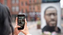 Seseorang mengabadikan foto mural George Floyd di Manchester tengah, Inggris (4/6/2020). George Floyd tewas kehabisan napas saat dalam penahanan pihak kepolisian Negara Bagian Minnesota, wilayah Midwest Amerika Serikat, pada pekan lalu. (Xinhua/Jon Super)