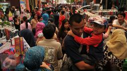 Warga memadati kawasan perbelanjaan Pasar Baru, Jakarta, Minggu (26/6). Menjelang lebaran sejumlah toko mulai memberikan potongan harga untuk menarik pembeli. (Liputan6.com/Gempur M Surya)