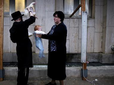 Seorang pria Yahudi Ultra-Ortodoks memegang ayam di atas kepala bayi saat melakukan ritual Kaparot, di Ashdod, Israel, (9/10). Dalam ritual ini ayam putih disembelih sebagai syarat simbolis dari penebusan. (REUTERS/Amir Cohen)