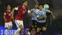 Penyerang Uruguay, Luis Suarez, berebut bola dengan bek Chile, Francisco Sierralta, pada laga kualifikasi Piala Dunia 2020 zona Amerika Selatan di Estadio Centenario, Jumat (9/10/2020) pagi WIB. Uruguay menang 2-1 atas Chile. (AFP/Raul Martinez/various sources)