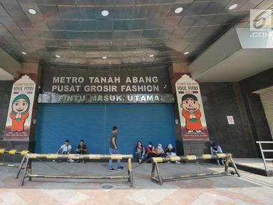 Sejumlah orang duduk di depan pintu masuk pasar Blok A Tanah Abang, Jakarta, yang tutup pada Kamis (23/5/2019). Pengelola Pasar Tanah Abang menutup sementara aktivitas perdagangan demi mengantisipasi dampak kericuhan Jakarta dalam beberapa hari ini. (Liputan6.com/Herman Zakharia)