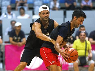 Bintang tenis Novak Djokovic (kanan) duel dengan Grigor Dimitrov dalam pertandingan persahabatan bola basket jelang Adria Tour di Zadar, Kroasia, Kamis (18/6/2020). Djokovic menggelar Adria Tour untuk mempromosikan olahraga hingga penggalangan dana. (Xinhua/Pixsell/Marko Dimic)