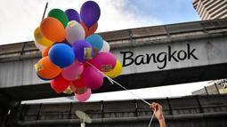 Seorang pengunjuk rasa memegang balon dengan pesan anti-pemerintah selama demonstrasi menentang usulan pembelian kapal selam oleh pemerintah yang berpihak pada militer di Bangkok (31/8/2020). (AFP/Lillian Suwanrumpha)