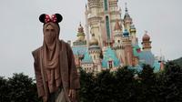 Seorang pengunjung yang mengenakan masker berpose untuk foto di Disneyland Hong Kong pada Jumat (25/9/2020). Setelah dibuka dan tutup kembali, Disneyland Hong Kong dibuka kembali untuk wisatawan. (AP Photo/Kin Cheung)