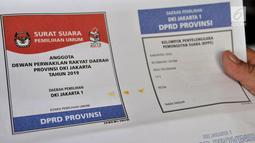 Petugas menunjukkan surat suara yang terkena bercak noda di Gedung Logistik KPU Kota Jakarta Pusat, Salemba, Jakarta, Selasa (5/3). Sebanyak 60 persen surat suara rusak akibat terpotong atau tidak simetris dan bercak noda. (merdeka.com/Iqbal Nugroho)