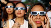 Warga mengunakan kacamata khusus menyaksikan proses Gerhana Matahari Total (GMT) 2016 di halaman Taman Ismail Marzuki (TIM), Jakarta, Rabu (9/3). Di Jakarta, gerhana matahari terjadi sebesar 88,76 persen selama sekitar 2. (Liputan6.com/Fery Pradolo)