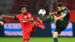 Gelandang Wolfsburg, Renato Steffen, berebut bola dengan bek Bayer Leverkusen, Wendell, pada laga pekan ke-28 Bundesliga di Stadion Bay Arena, Selasa (26/5/2020) waktu setempat. Wolfsburg menang 4-1 atas Bayer Leverkusen. (AFP/Marius Becker/POOL)