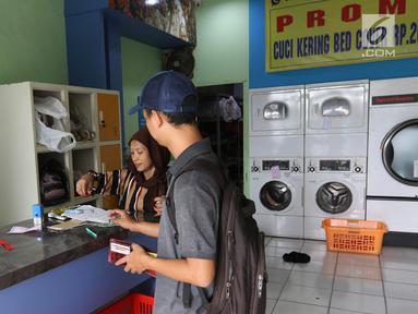 Pekerja melayani pelanggan di toko laundry di Jakarta, Rabu (20/6). Libur lebaran banyak jasa laundry kebanjiran order hingga 100 karena banyaknya para pembatu rumah tangga yang mudik lebaran. (Liputan6.com/Angga Yuniar)