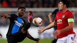 Pemain Club Brugge,  Emmanuel Bonaventure (kiri) berebut bola dengan bek Manchester United, Harry Maguire dalam leg pertama babak 32 besar Liga Europa di Jan Breydelstadion, Kamis (20/2/2020). Manchester United gagal meraih hasil maksimal usai ditahan imbang Club Brugge 1-1. (JOHN THYS / AFP)