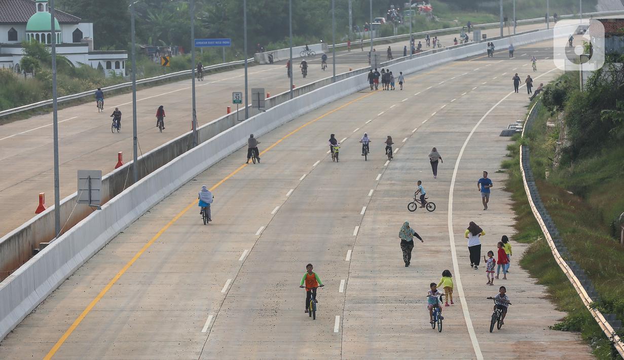Warga berolahraga sepeda dan berlari pada waktu sore di kawasan pembangunan Tol Serpong Kunciran, Ciputat, Tangerang Selatan, Kamis (25/6/2020). Pembangunan tol yang belum rampung dimanfaatkan sejumlah warga beraktivitas selama pandemi Covid-19. (Liputan6.com/Fery Pradolo)
