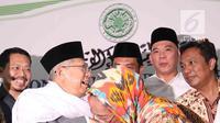 Budayawati Sukmawati Soekarnoputri mengenakan kerudung berwarna oranye mencium tangan Ketua MUI KH Ma'ruf Amin usai pertemuan dengan MUI di kantor MUI, Jakarta, Kamis (5/4). (Liputan6.com/Angga Yuniar)