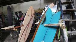 Seorang pria merapihkan papan selancar di sebuah pabrik dekat Kuta di pulau Bali (18/12). Biasanya, pengerjaan sebuah papan surfing memakan waktu hingga dua minggu tergantung ukuran. (AFP Photo/Sonny Tumbelaka)