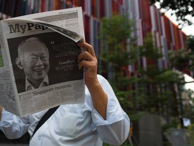 Seorang pria membaca koran setelah sehari meninggalnya mantan PM Singapura, Lee Kuan Yew, Singapura, Selasa (24/3/2015). Lee meninggal pada hari Senin (23/3) di usia 91 tahun dan wajahnya menghiasi berbagai media cetak Singapura. (AFP PHOTO/Mohd RASFAN)
