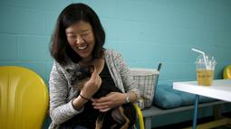 Pengunjung bermain dengan seekor anjing sambil menikmati minumannya saat pembukaan Dog Cafe coffee shop di Los Angeles, AS (7/4). Anjing di kafe ini juga dapat diadopsi oleh pengunjung sebagai peliharaan yang dilindungi. (REUTERS/Lucy Nicholson)
