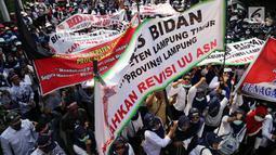 Pegawai Non PNS yang tergabung dalam KNASN (Komite Nusantara Aparatur Sipil Negara) dan Forum Honorer Kategori 2 Indonesia (FHK2I) mebentangkan spanduk saat melakukan aksi unjuk rasa di Kantor Kemenpan RB, Jakarta, Rabu (2/5). (Liputan6.com/Johan Tallo)