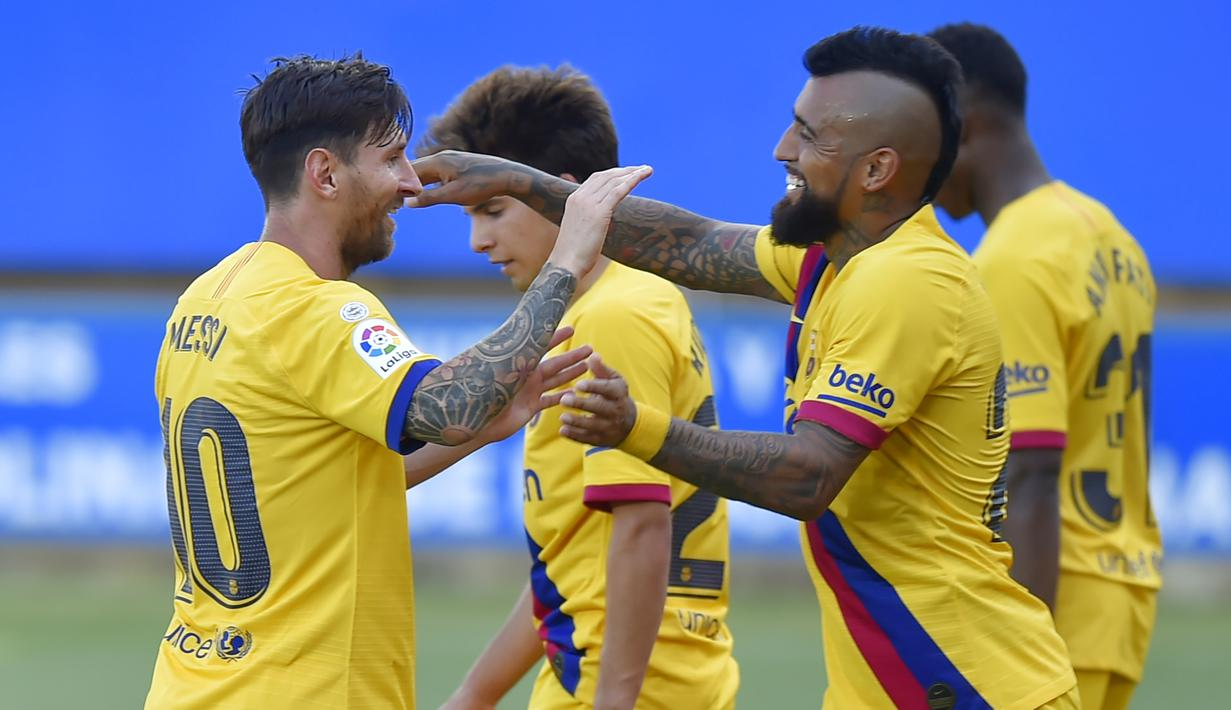 Pemain Barcelona, Lionel Messi dan Arturo Vidal merayakan gol ke gawang Alaves pada laga La Liga di Stadion Mendizorroza, Minggu (19/7/2020). Barcelona menang dengan skor 5-0. (AFP/Ander Gillenea)