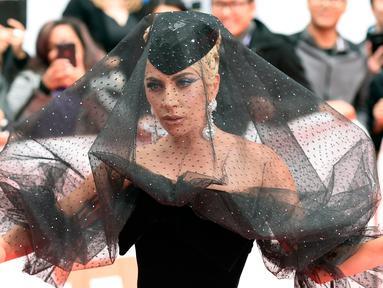 """Lady Gaga berpose di karpet merah saat tiba menghadiri pemutaran film """"A Star is Born"""" selama Toronto International Film Festival 2018 di Toronto (9/9). Lady gaga tampil menggenakan gaun berwarna hitam. (AP Photo/Nathan Denette)"""