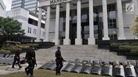 Personel kepolisian saat berjaga di depan Gedung Mahkamah Konstitusi (MK), Jakarta, Rabu (26/6/2019). Kepolisian memperketat penjagaan di sekitar Gedung MK dengan kawat berduri, kendaraan lapis baja, serta ratusan personel. (merdeka.com/Iqbal S. Nugroho)