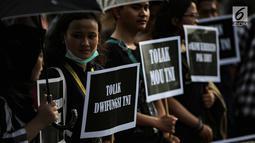 Aktivis Jaringan Solidaritas Korban untuk Keadilan (JSKK) menyuarakan tuntutan saat Aksi Kamisan ke-576 di depan Istana Merdeka, Jakarta, Kamis (28/2). Mereka menolak kembalinya militer untuk menduduki jabatan sipil. (Liputan6.com/Faizal Fanani)