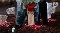 Petugas memasang nisan jenazah dengan protokol COVID-19 di TPU Tegal Alur, Jakarta, Kamis (31/12/2020). Berdasar data yang dikeluarkan, Kamis (31/12) total kasus COVID-19 di Indonesia sejak Maret lalu mencapai 743.198 orang, 611.107 sembuh, 22.138 meninggal dunia. (Liputan6.com/Helmi Fithriansyah)