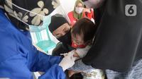 Perawat dibantu kader Posyandu menyuntikan vaksin campak, vaksin pentabio berisi vaksin DPT, Hepatitis B dan Haemophilus Influenzae dan Imunisasi Polio terhadap anak di RW 09, Kelurahan Pondok Benda, Tangerang Selatan, Senin (14/12/2020). (merdeka.com/Dwi Narwoko)