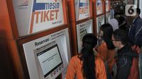 Calon penumpang membeli tiket kereta Mudik Lebaran 2020 melalui mesin E-Kios di Stasiun Pasar Senen, Jakarta, Senin (17/2/2020). PT Kereta Api Indonesia resmi membuka penjualan tiket Mudik Lebaran 2020 mulai 14 Februari 2020. (merdeka.com/Iqbal Nugroho)
