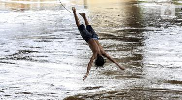Seorang anak melompat ke Sungai Ciliwung saat banjir melanda Jalan Bina Warga Rt 005/Rw 07 Kelurahan Rawa Jati, Jakarta, Senin (8/2/2021). Banjir setinggi 60-190 cm tersebut disebabkan oleh luapan air Sungai Ciliwung dan curah hujan Jakarta yang tinggi. (Liputan6.com/Johan Tallo)