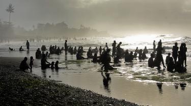 Sejumlah warga menjalani prosesi menyucikan diri saat Hari Banyu Pinaruh di pantai Keramas, Gianyar, Bali, Minggu (12/5/2019). Hari Banyu Pinaruh merupakan hari yang diyakini oleh umat Hindu sebagai waktu yang baik untuk menyucikan diri secara spritual dengan mandi di mata air  (SONNY TUMBELAKA/AFP)