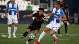 Gelandang Sevilla, Olivier Torres, berebut bola dengan penyerang Leganes, Javier Aviles, pada laga lanjutan La Liga pekan ke-33 di Estadio Municipal de Butarque, Rabu (1/7/2020) dini hari WIB. Sevilla menang 3-0 atas Leganes. (AFP/Pierre-Philippe Marcou)