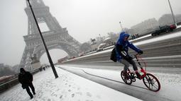 Seorang pengendara melintas saat turun salju di Paris, Prancis, (6/2). Sebelumnya Paris mengalami banjir bandang  akibat meluap Sungai Seine yang dipicu oleh curah hujan tinggi. (AP Photo / Francois Mori)