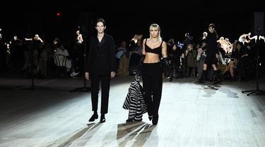 Miley Cyrus (kanan) berjalan di catwalk untuk show Marc Jacobs Fall 2020 selama New York Fashion Week di New York City, Rabu (12/2/2020). Miley Cyrus bergabung dengan sejumlah model di runway termasuk, Gigi Hadid dan adiknya, Bella Hadid serta Kaia Gerber. (JAMIE MCCARTHY/GETTY IMAGES /AFP)