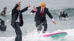 Gary Crane berselancar mengenakan kostum menyerupai Presiden AS, Donald Trump di Newport Beach, California, 28 Oktober 2017. Acara ini untuk merayakan Halloween yang jatuh pada tanggal 31 Oktober. (Paul Rodriguez/The Orange County Register via AP)