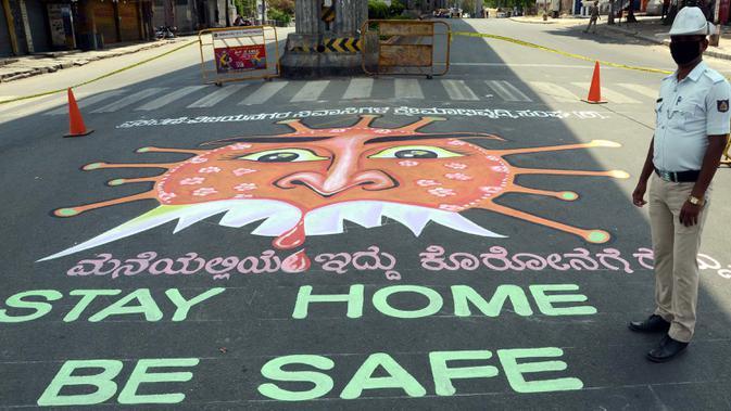 Petugas kepolisian India berdiri disamping grafiti yang mengilustrasikan virus  corona di Bangalore (3/4/2020). Grafiti tersebut dibuat untuk meningkatkan kesadaran masyarakat agar mematuhi lockdown yang diberlakukan pemerintah India  sebagai langkah pencegahan COVID-19. (Xinhua/Stringer)