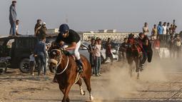 Sejumlah joki memacu kudanya saat bersaing dalam balap kuda di Rafah, Jalur Gaza, Palestina, Selasa (10/9/2019). Balapan kuda tradisional Palestina tersebut digelar di bekas lokasi bandara Jalur Gaza yang telah hancur. (AFP Photo/Said Khatib)