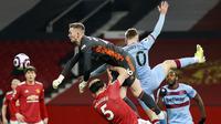 Kiper Manchester United, Dean Henderson, berusaha menghalau bola saat melwan West Ham United pada laga Liga Inggris di Stadion Old Trafford, Minggu (15/3/2021). Setan Merah menang dengan skor 1-0. (AP/Clive Brunskill,Pool)