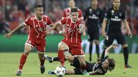 Pemain Real Madrid, Luka Modric jatuh saat berebut bola dengan pemain Bayern, Thiago dan James Rodriguez pada leg pertama semfinal Liga Champions di Allianz Arena, Munich, (25/4/2018). Real Madrid menang 2-1. (AP/Matthias Schrader)