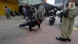 Petugas gabungan memberikan hukuman push up kepada warga yang tidak memakai masker saat razia Pembatasan Sosial Berskala Besar (PSBB) di Kawasan Jalan Fatmawati, Jakarta, Selasa (28/4/2020). Penertiban terkait pelaksanaan PSBB Jakarta dan memutus rantai penyebaran COVID 19. (merdeka.com/Imam Buhori)